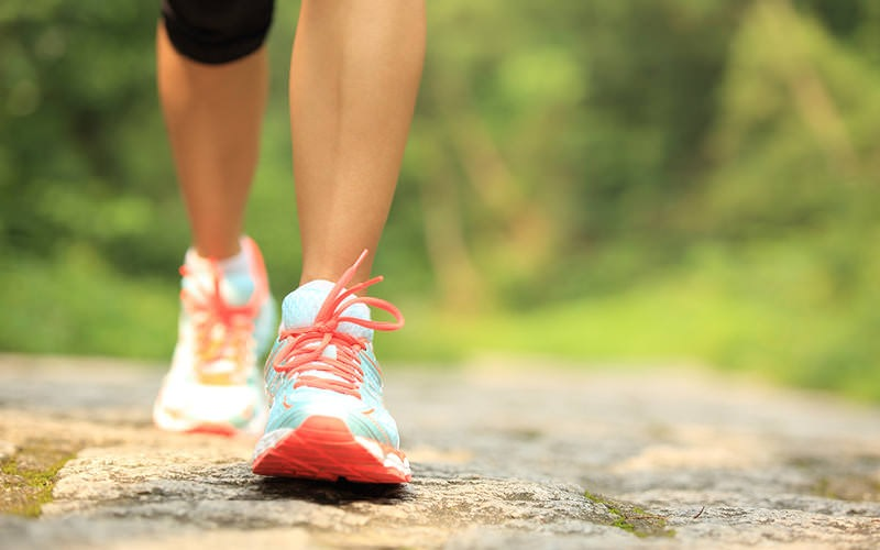 woman in running shoes walks along path